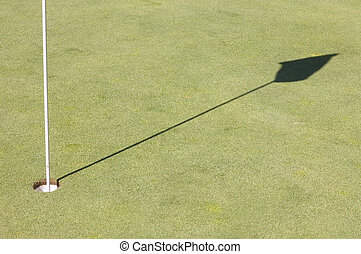 Shadow of a golf green flag on the green