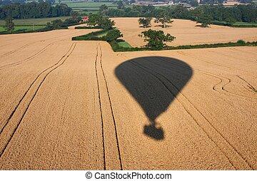 Shadow of a hot air balloon flying over rural farmland