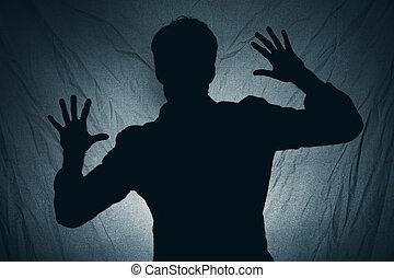 Shadow of a man behind dark fabric