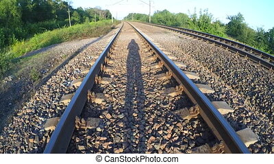 Shadow of a man walking on a railway.
