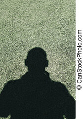 Shadow of a photographer in the succer field background