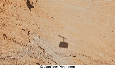 Shadow of a ropeway cabin rising in Masada desert. Aerial...