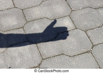 Shadow of human arm and hand with thumb-up success gesture on gray pavement lit by bright sun.
