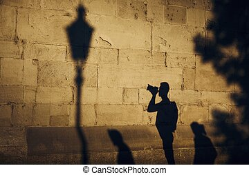 Shadow of photographer on stone wall