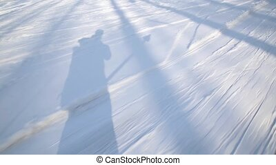 shadow of skiers on a snow. T-bar ski lift pull skiers to...