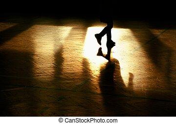 Shadow of sportsman. Window curtain wall reflecting in worn parquet floor at school gym.