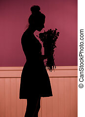 Shadow of the woman holding a bouquet of flowers
