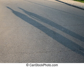 Shadow of two people on the road in the evening