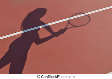Shadow of young adult woman with racket