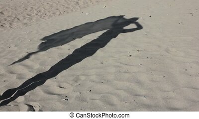Shadow on a sand of slim young girl with pareo on a wind -...