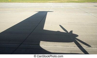 Shadow on runway strip commercial screw aircraft. View from...