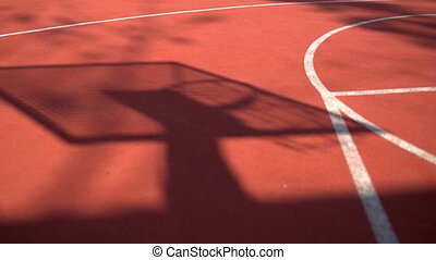 Shadow on the court of basketball basket with chains on...