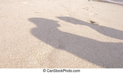 shadow on the sand Couple of lovers kissing on the beach on a clear sunny day.  slow motion