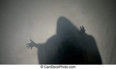 Shadow silhouette of a dark halloween ghost dancing in fog behind the glass