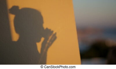 shadow silhouette of a woman drinking beverage from glass