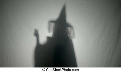 Shadow silhouette of an evil witch dialing a phone number...