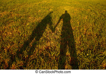shadow silhouette of couple holding hands on meadow at sunset