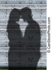 Shadows of couple embracing on wooden boards wall
