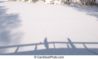 Shadows of couple, snow background. Silhouettes of people...