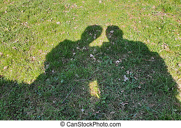 Shadows of lovers sitting in the park on a bench