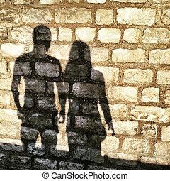 Shadows of man and woman on a brick wall