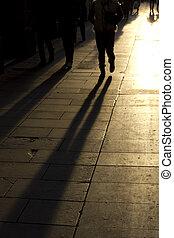 shadows of people walking down the street