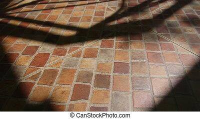 Shadows on terrace ceramic tiled floor in sunny day