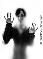 Shadowy woman figure behind a frosted glass