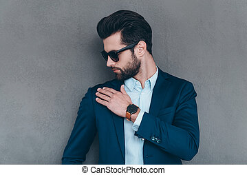 Shake it off. Close-up of young handsome man in sunglasses shaking off invisible dust from his shoulder while standing against grey background
