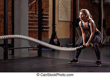 young pleasant girl training power by slamming the ropes