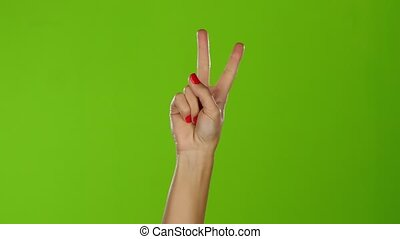 Shaking girl hand gesture denoting the peace. Green screen...