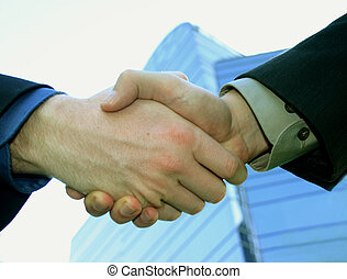 Business men shaking hands in front of a building