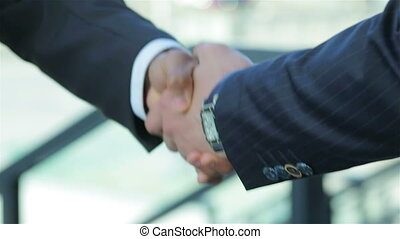 Shaking hands confidently outdoors
