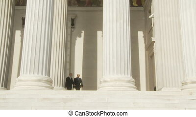 shaking hands front view - two businessman coming out of...