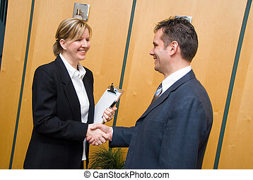 Shaking hands - man and woman greeting each other in a...