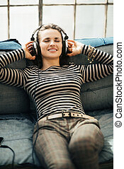 Happy young woman listening to the music through headphones...