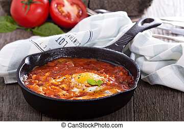 Shakshuka with tomatoes and eggs in a cast iron pan