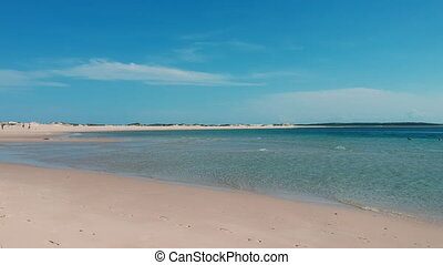 Shallow Beach Water and Sand with Horizon over Land