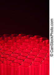 Shallow focus close-up of empty glass test tubes in red