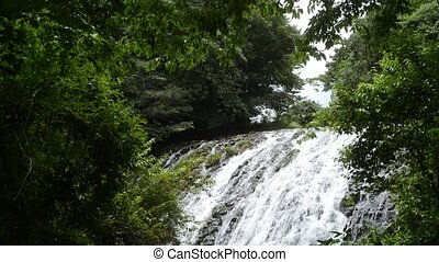 Shallow waterfall flowing down rocky slope which surrounded ...