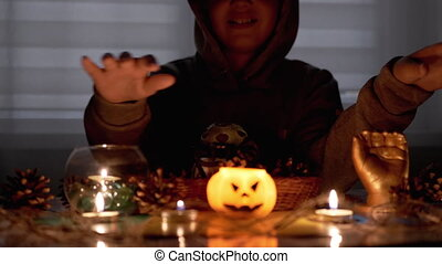 Shaman Boy with in Hood Performs Rite by Candle in Dark Room on Halloween. Silhouette of Boy. Creepy, dark mysterious night ambiance. Concept of children's party. Decorations with a pumpkin. 4K