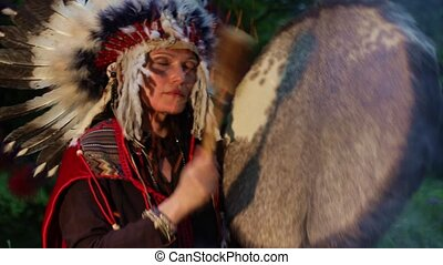Shaman woman playing shaman frame drum at night in the forest