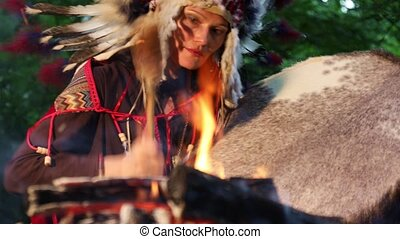 Shaman woman  in native American Indian headdress playing shaman frame drum at night in the forest