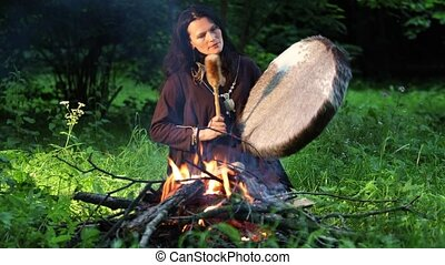 Shamanic ritual at night in the forest by the fire. Ethnic traditions