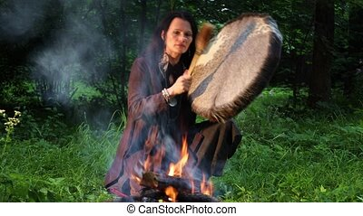 Shamanic woman conducts ritual at night in the forest by the fire. Ethnic traditions
