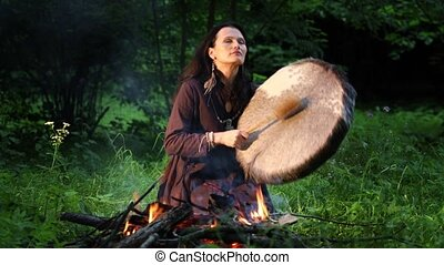 Shamanic woman conducts ritual at night in the forest by the fire