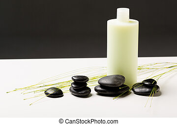shampoo bottle, massage stones and green plant - spa, health...