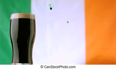 Shamrock confetti falling beside pint of stout on irish flag...