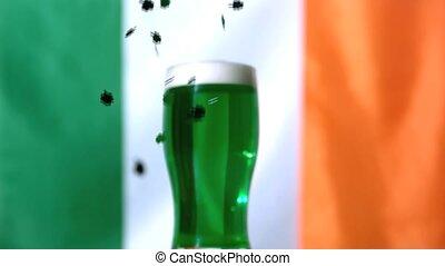Shamrock confetti falling beside pint of green beer in slow...