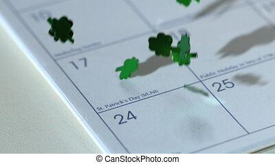 Shamrock confetti falling on calander in slow motion marking...
